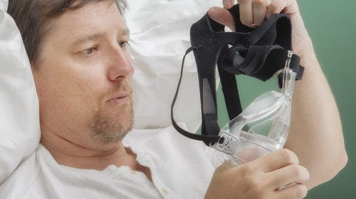 Image of a man holding a CPAP Mask bt Fisher and Paykel